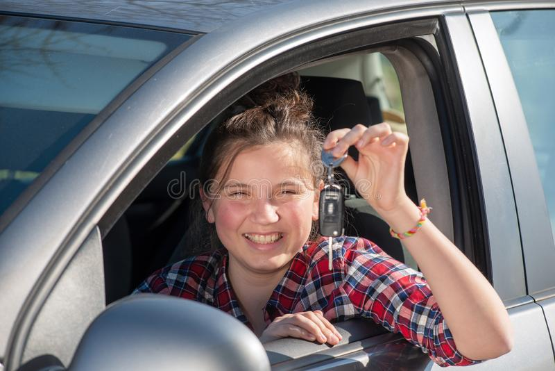 Young teenage girl sitting in the car, showing keys stock photography
