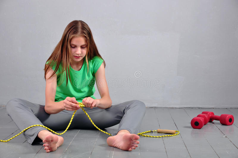 Young teenage girl sitting on the floor with skipping rope and dumbbells relaxing having rest in studio. Young muscular teenage girl sitting on the floor with royalty free stock photography