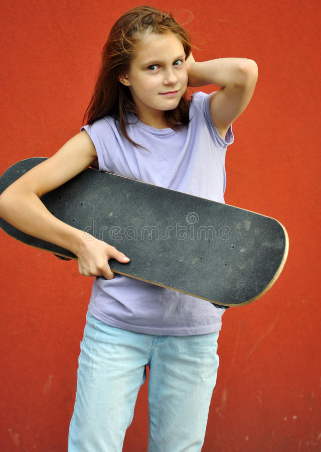 Young teenage girl with skateboard in the street stock photo