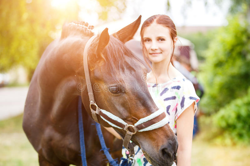 Young teenage girl standing with her bay mare. Young smiling teenage girl standing with her bay mare royalty free stock photography