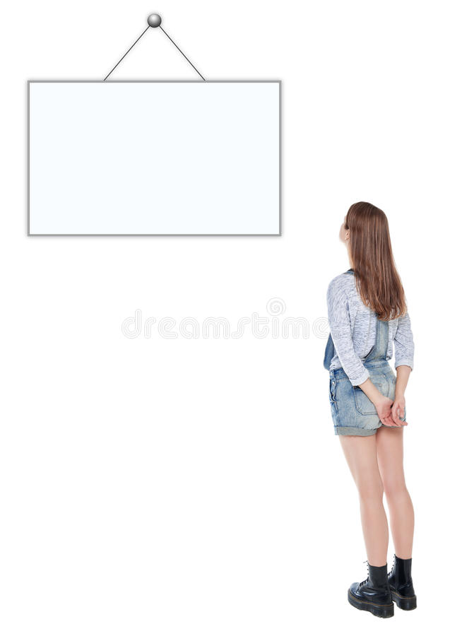 Young teenage girl standing and looking on empty picture frame stock image