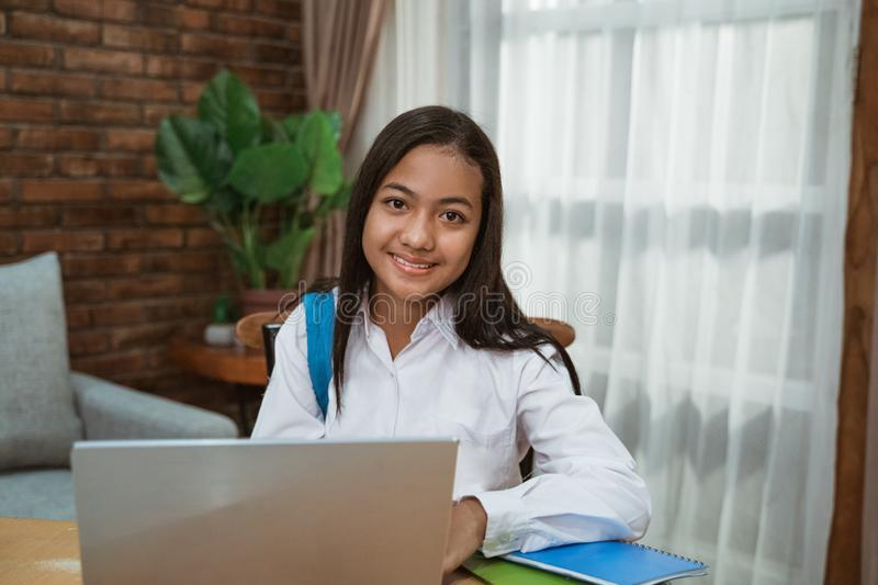 Young teenage girl using laptop. Junior high school student of indonesia doing homework royalty free stock photography