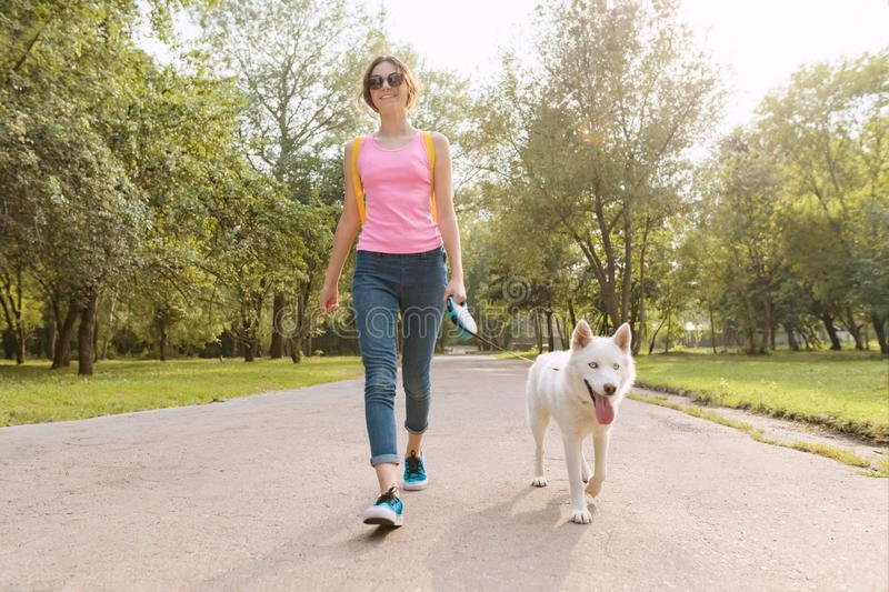 Young teenage girl walking with a dog in the park stock photo