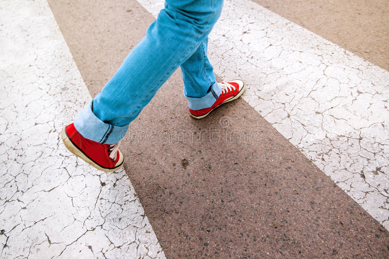 Young teenage person walking over pedestrian zebra crosswalk. Young teenage person wearing blue jeans and red sneakers, walking over pedestrian zebra crosswalk stock image