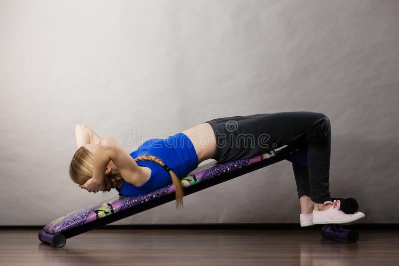 Woman training on bench for sit ups. Young teenage woman training on bench for sit ups at home. Being fit and healthy, stomach muscles workout stock photography