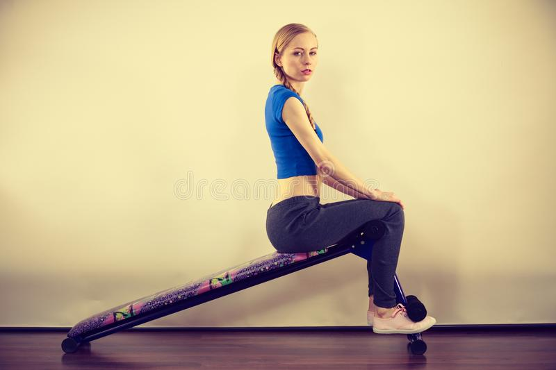 Woman training on bench for sit ups. Young teenage woman training on bench for sit ups at home. Being fit and healthy, stomach muscles workout stock image
