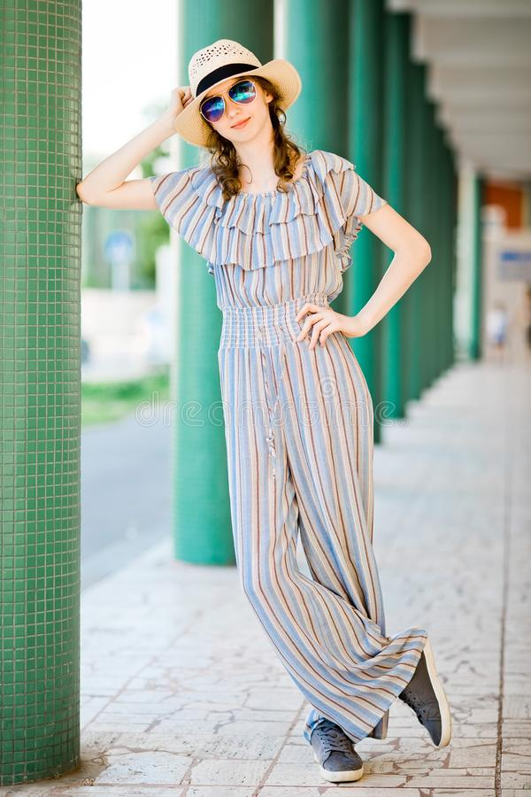 Young teenaged girl in jumpsuit dress posing at colonnade royalty free stock photography