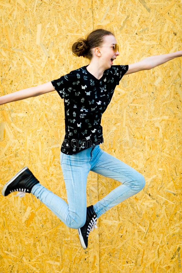 Young teenaged girl jumping in front of fence stock images
