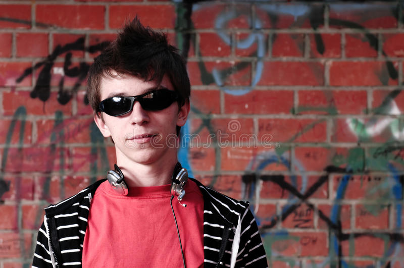 Young Teenager against Graffiti Wall. Young Teenager with sunglasses and headphones against Graffiti Wall royalty free stock photo