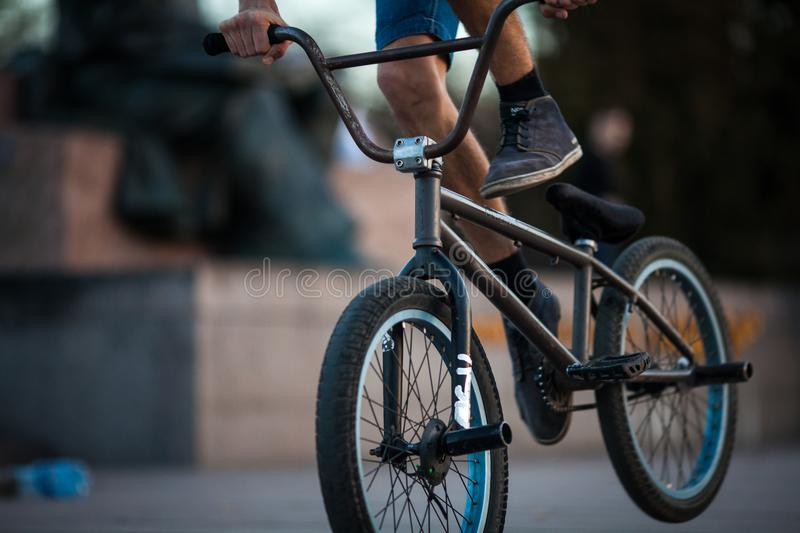 Young teenager bicyclist boy riding on beautiful orange bmx bicycle male hobby extreme sport male hobby lower part closeup backgro royalty free stock photography