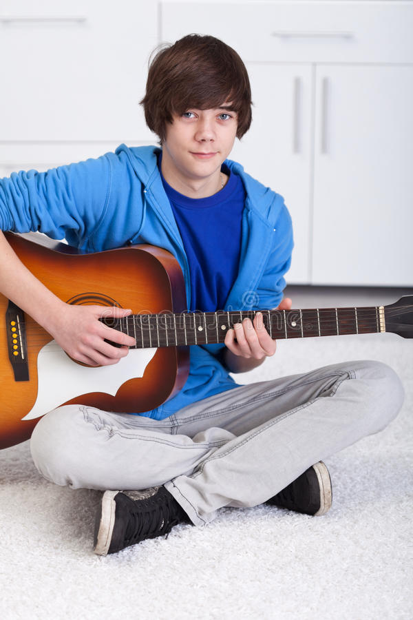 Young teenager boy playing the guitar stock images
