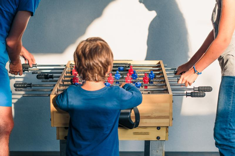 Young teenager boy playing table football with another player. Young people having fun, spending time together stock photos