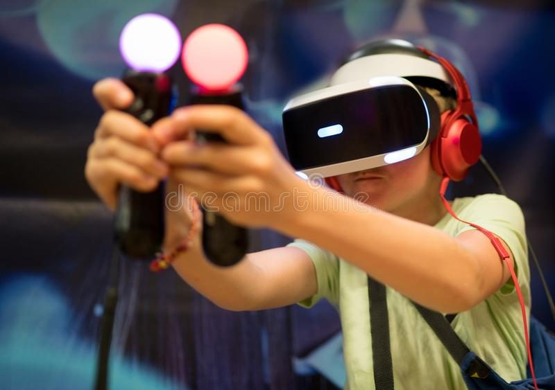 Young teenager boy using a Virtual reality headset with goggles and hands motion controllers in playing game zone. Modern. Technologies concept image stock images