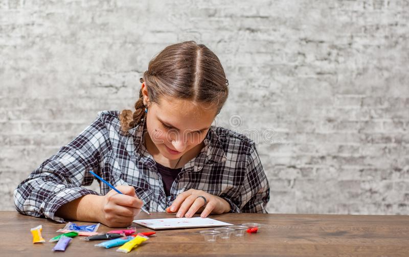 Young teenager brunette girl with long hair drawing with brush at a table on gray wall background with copy space. royalty free stock images