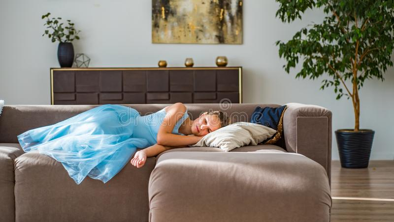 Teenager brunette girl with long hair lying on sofa at home. Young teenager brunette girl with long hair lying on sofa at home royalty free stock images