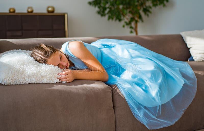 Teenager brunette girl with long hair lying on sofa at home. Young teenager brunette girl with long hair lying on sofa at home stock photography