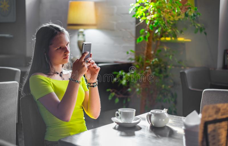 Young teenager brunette girl with long hair sitting indoor in urban cafe and use her smartphone stock image