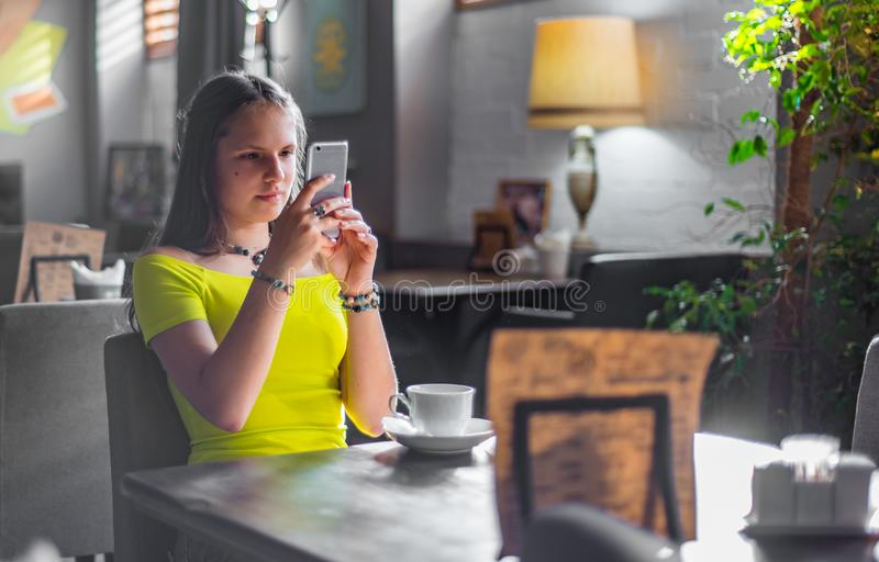 Young teenager brunette girl with long hair sitting indoor in urban cafe and use her smartphone royalty free stock image