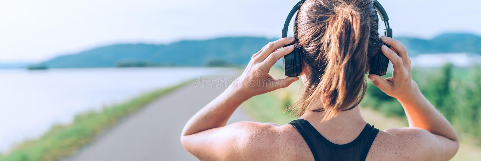 Young teenager girl adjusting  wireless headphones before starting jogging and listening to music. Web page header cropping royalty free stock photo
