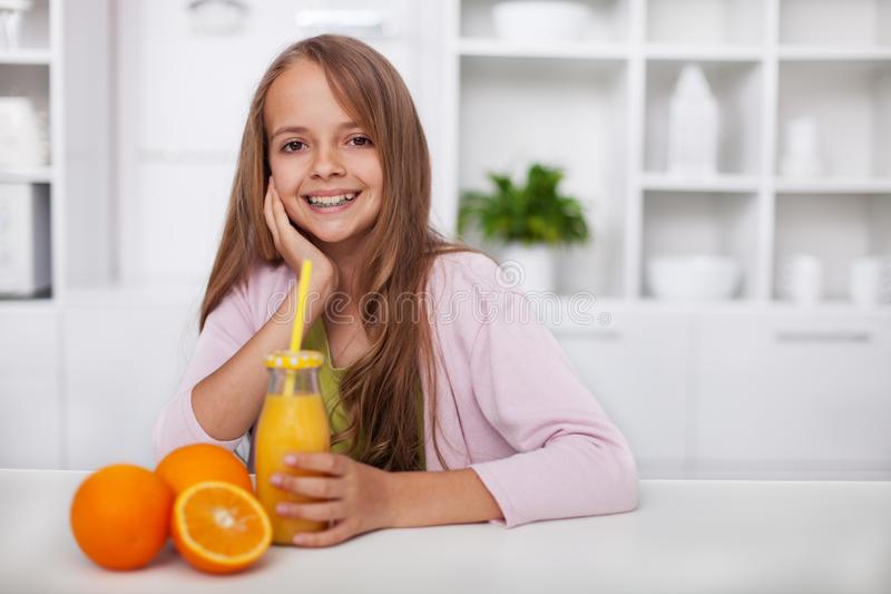 Young teenager girl with broad smile and freshly squeezed orange juice in the kitchen stock photography