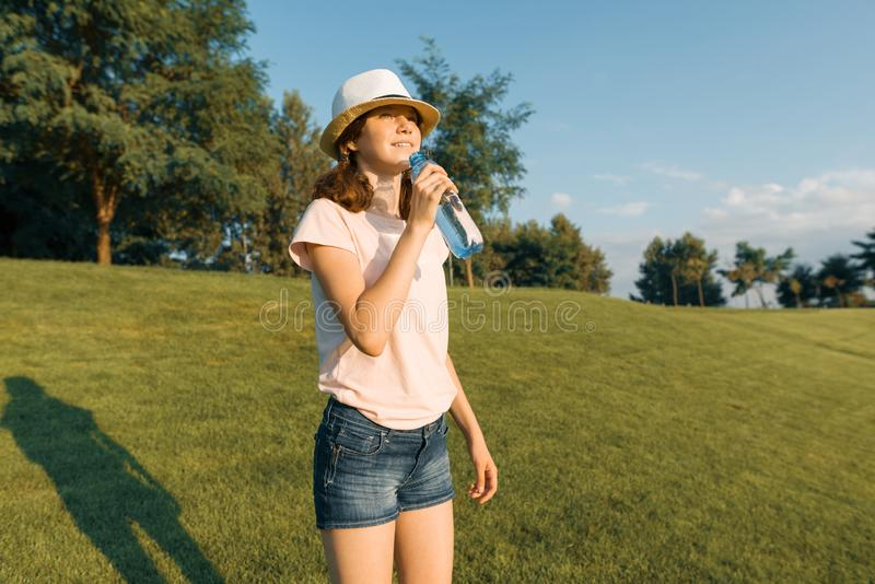 Young teenager girl drinks refreshing water from a bottle on a hot summer day, walking in the park, the golden hour.  royalty free stock images