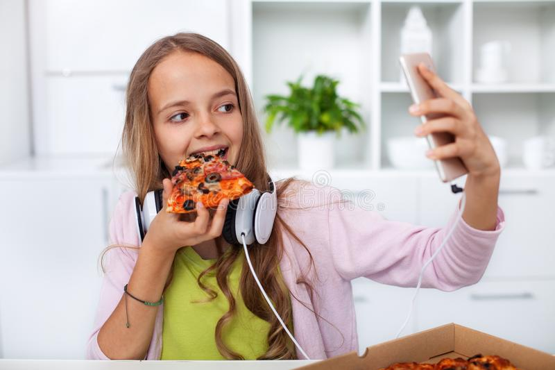 Young teenager girl eating pizza in the kitchen - making a selfie stock images