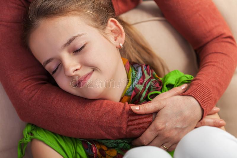 Young teenager girl enjoys communion with her mother arms holding her stock photo