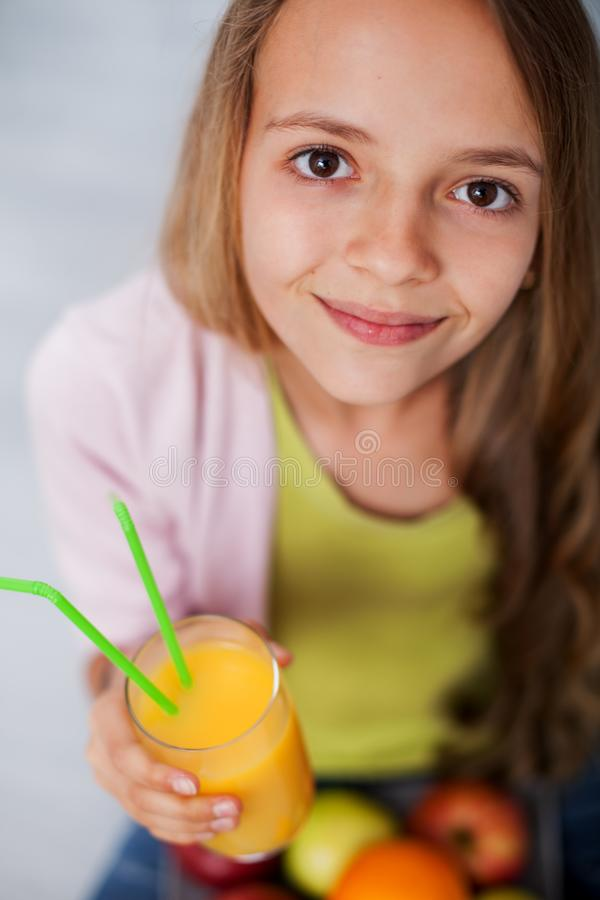 Young teenager girl with a glass of fresh fruit juice royalty free stock images