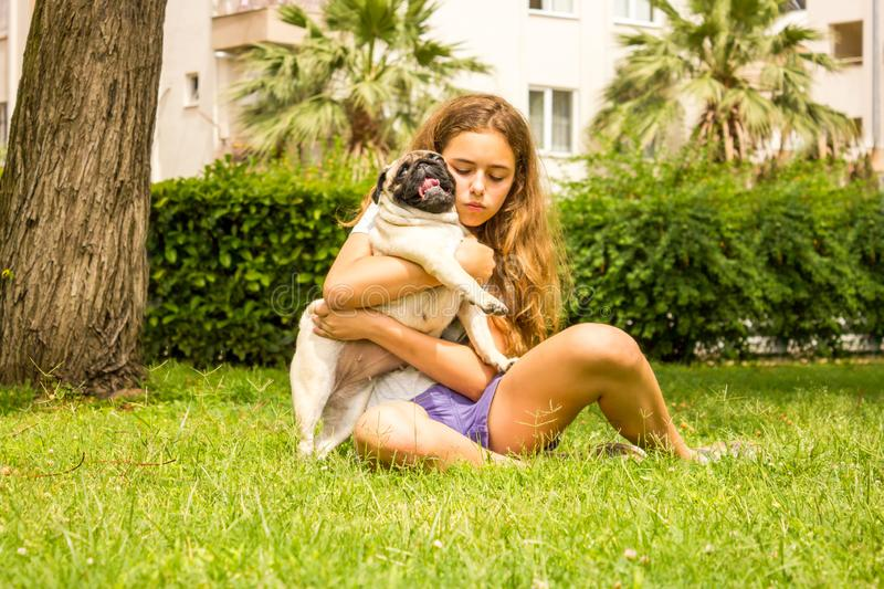 Young teenager girl hugs her pug dog in the park on the green grass stock images