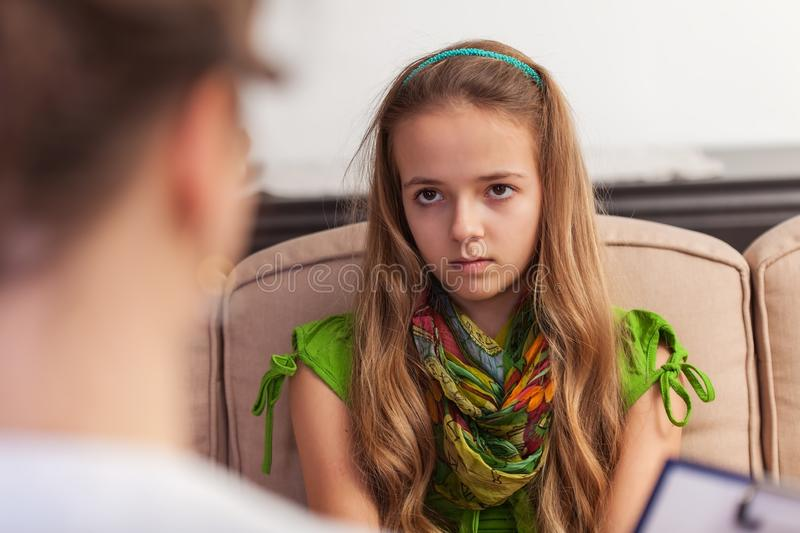 Young teenager girl looking with disbelief and bored, sitting at counseling. In front of professional woman assessing her - close up royalty free stock photography