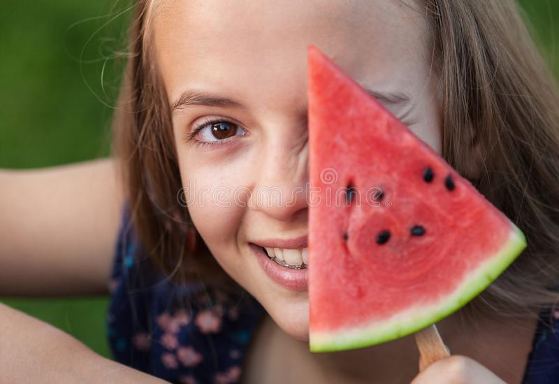 Young teenager girl playing with a slice of watermelon stock photos