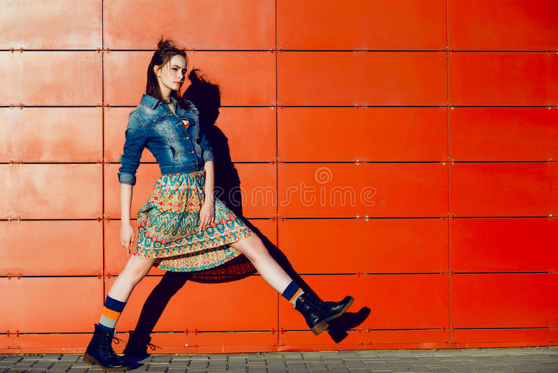 Young teenager girl posing, going, runs near urban red wall background in skirt and jeans jacket on the sunset. Beautiful young teenager hipster girl posing stock photo