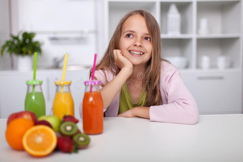 Young teenager girl sitting in the kitchen with bottles of freshly squeezed fruit juices stock image