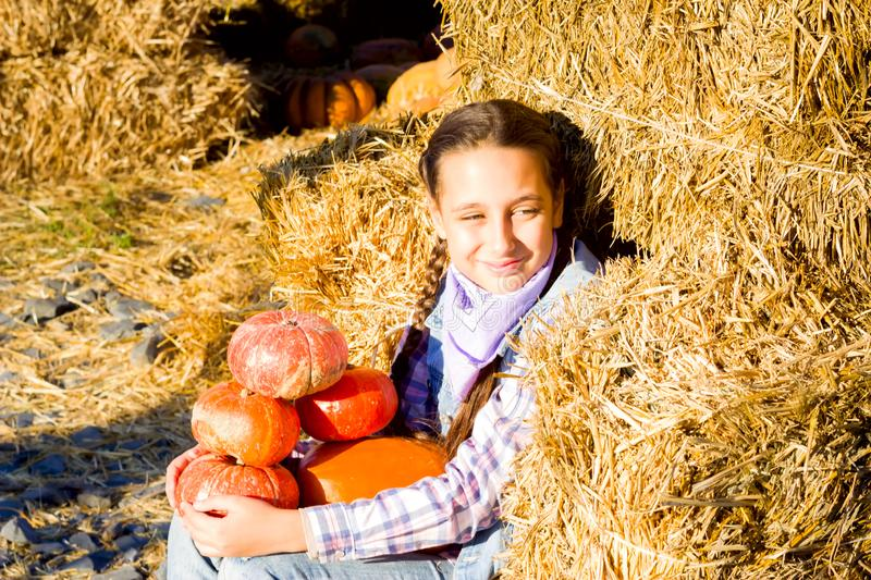 Young teenager girl sitting on straw with pumkins on farm market. Family celebrating thanksgiving or halloween. royalty free stock images