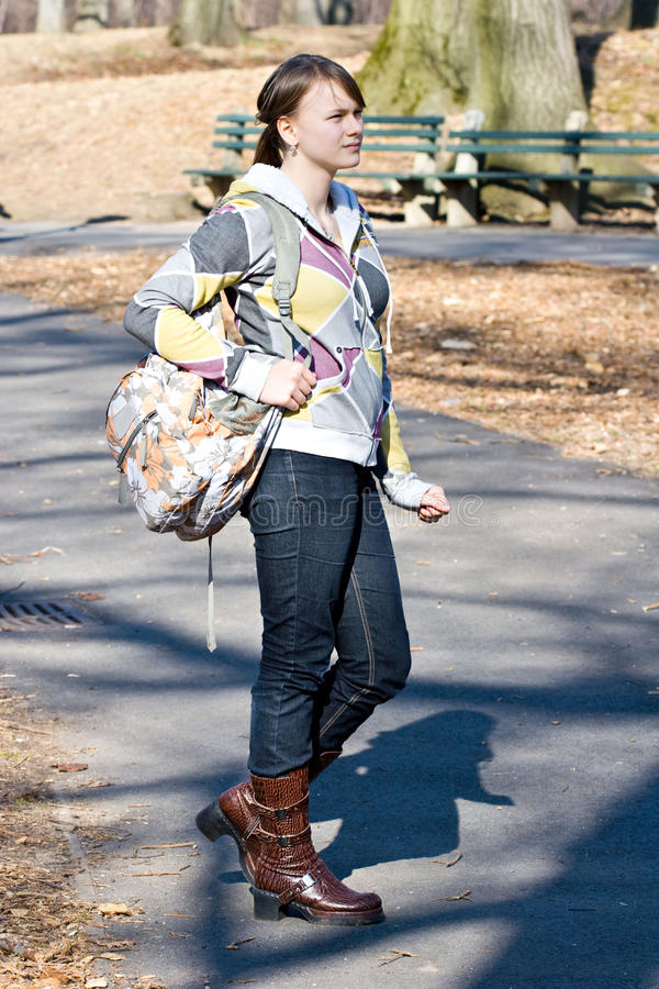 Young teenager girl standing holding a book bag