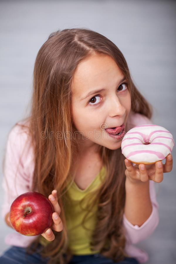 Young teenager girl tempted by the sugary food royalty free stock photography