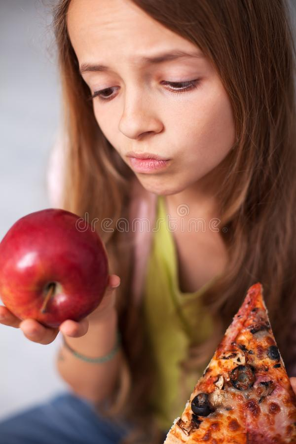Young teenager girl undecided between healthy fresh apple and ap stock image