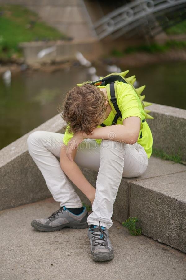 A young teenager guy is suffering from a headache. he keeps his hands to his head and winces of discomfort, sitting on the nature. One royalty free stock image