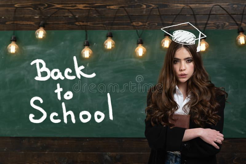Young teenager with school books. Cute schoolgirl posing solving problem on blackboard. Ready for school. stock images
