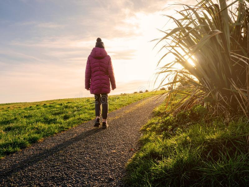 Young teenager walking on a path at sunset. Sun flare, calm and peaceful atmosphere. Cloudy sky stock images