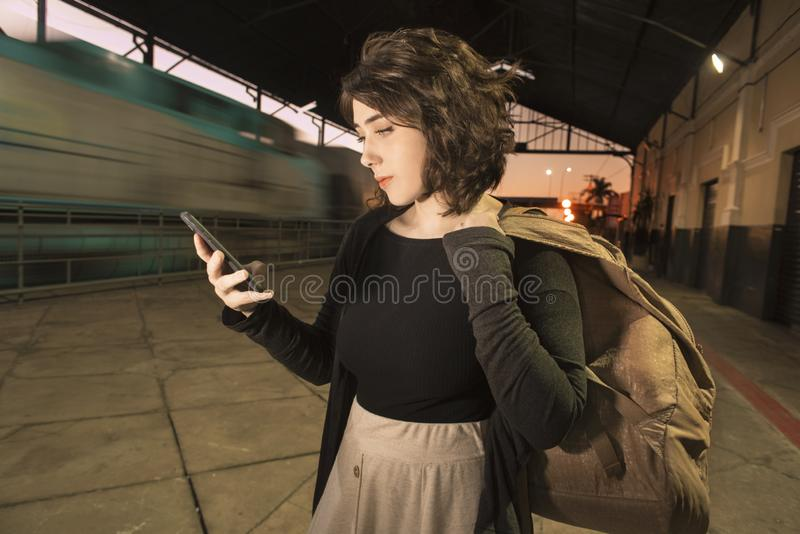 Young teenager woman with backpack alone at train station cheking smart phone at evening light stock image
