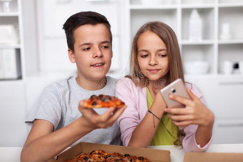 Young teenagers taking a selfie with their pizza in the kitchen royalty free stock images