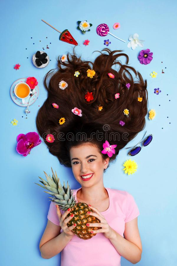 Young teens model holding a pineapple, lying on floor, on blue background. with makeup and hairstyle, flowers on hair. stock photos