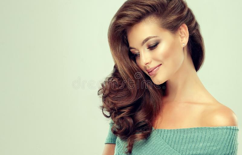 Light  smile on the face of young, brown haired beautiful model with long,  curly, well groomed hair.Hairdressing art, hair care. stock photography