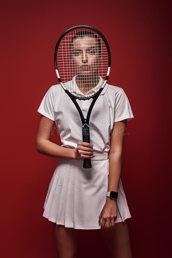 All it takes is all you've got! Young tennis player standing isolated over red background with a racket and a ball royalty free stock images