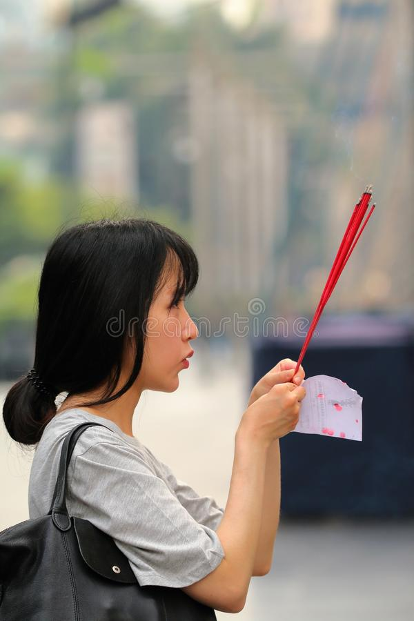 Young Thai lady praying at the Trimurti Shrine, Lover`s shrine, God of Love stock photo