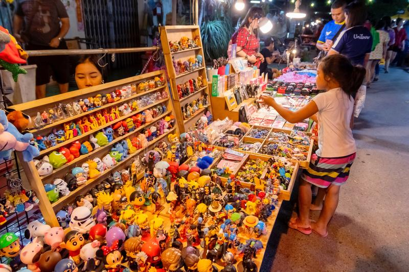 Young Thai girl are choosing some toys from the toy shop with variety of cartoon miniatures on the street market at Pranburi, stock images