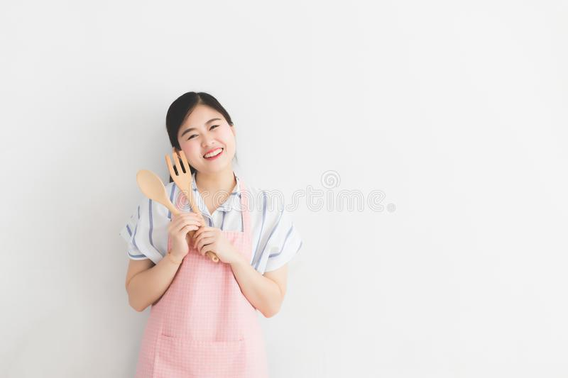 A young Thai woman, white skin, long hair, wearing a casual dress and pink apron, holding a kitchenware on a white wall. royalty free stock photography
