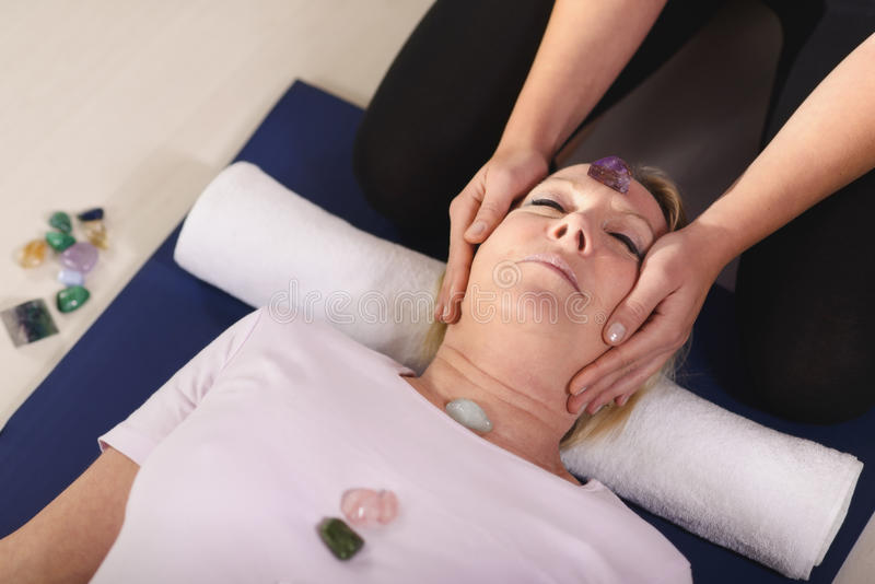 Young therapist arranging crystals on female client for reiki th stock image