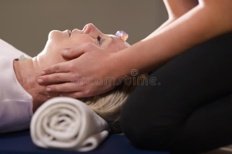 Young therapist arranging crystals on female client for reiki th royalty free stock image